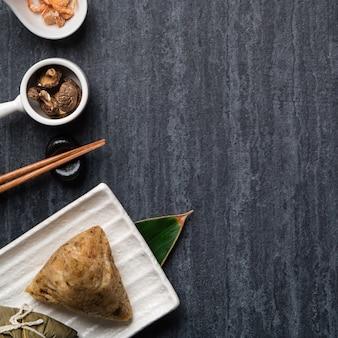 Zongzi. gnocco di riso vista dall'alto concetto di design per il tradizionale cinese dragon boat festival (duanwu festival) su sfondo ardesia nero scuro.