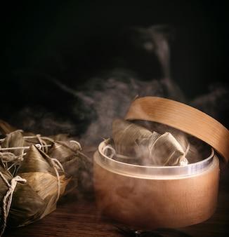 Zongzi, gnocchi di riso al vapore in piroscafo sulla tavola di legno, famoso cibo gustoso nel concetto di design di dragon boat festival duanwu, primi piani, copia dello spazio.