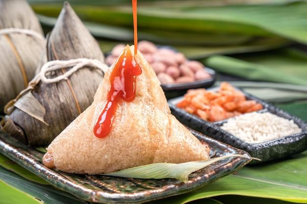 Zongzi, gnocchi di riso al vapore con salsa al peperoncino. primo piano, copia spazio, famoso cibo gustoso asiatico nel festival di duanwu di dragon boat