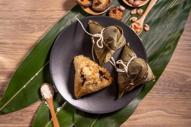 Zongzi, gnocchi di riso al vapore sul tavolo di legno foglie di bambù, cibo in dragon boat festival duanwu concept, close up, copia spazio, vista dall'alto, piatto lay