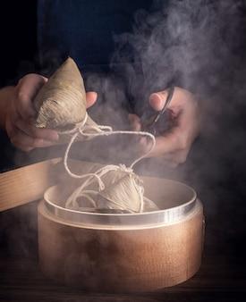 Zongzi, donna che andrà a mangiare gnocchi di riso al vapore sul tavolo di legno, famoso cibo gustoso nel concetto di design di dragon boat festival duanwu, vicino, spazio di copia