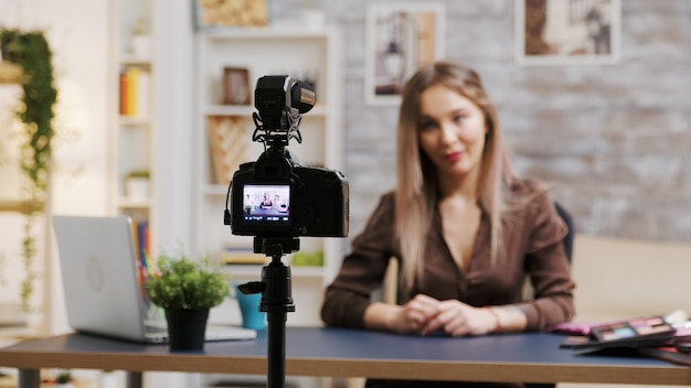 Ingrandisci l'inquadratura della truccatrice femminile che registra un vlog su una videocamera professionale