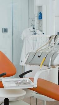 Ingrandisci l'inquadratura dell'attrezzatura medica ortodontica in un moderno ufficio luminoso, un trapano per stomatologia e altri strumenti professionali per la cura dei denti per la salute dentale