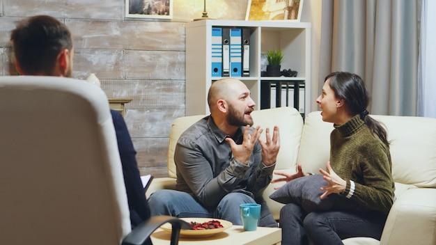 Inquadratura ingrandita di una giovane coppia che litiga alla consulenza per le relazioni. giovane moglie stressata.