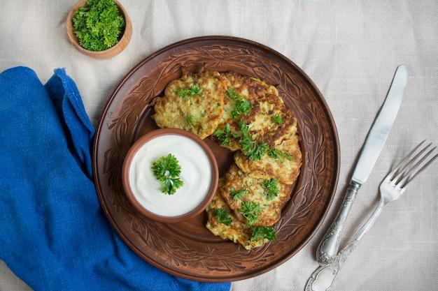 Zucchine fritte. crepes di zucchine vegetariane servite con erbe fresche e panna acida. sfondo chiaro.