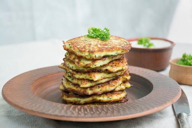 Zucchine fritte. frittelle di zucchine vegetariane servite con erbe fresche e panna acida. una pila di frittelle. sfondo chiaro.