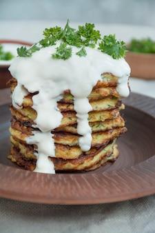Zucchine fritte. frittelle di zucchine vegetariane con erbe fresche e panna acida. una pila di frittelle. tavolo da pranzo. equilibrare il cibo sano. sfondo chiaro.