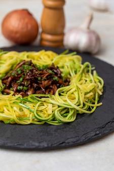 Spaghetti di zucchine con shimeji su lastra di pietra nera.