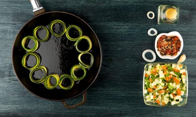 Zucchine in tavola. zucchine affettate giovani fritte in una pentola su una tavola scura. la vista dall'alto. copia spazio