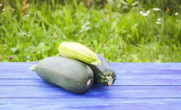 Verdure zucchine su tavole di legno all'aperto.