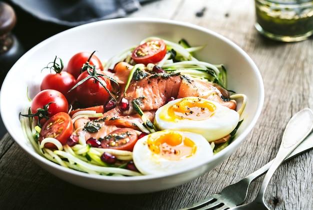 Zucchine zoodle con salmone affumicato, uovo sodo, insalatiera al melograno con condimento al pesto