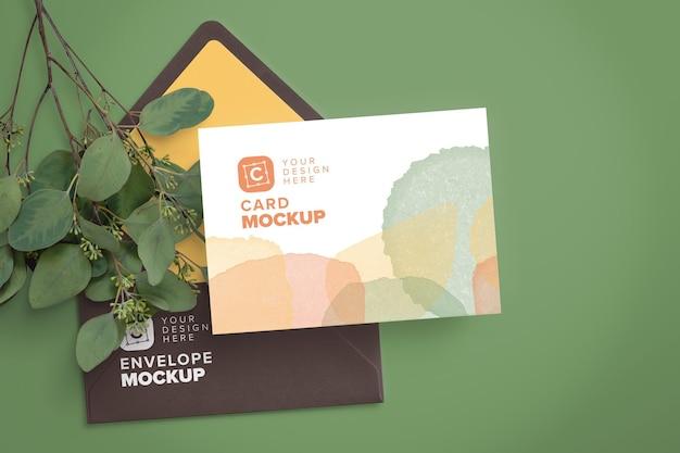 Mockup di carte 5x7in su busta e ramo di eucalipto