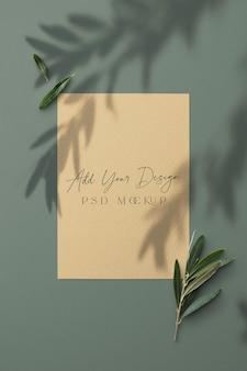 Mockup di carta 7x5 pollici con ombra sovrapposta sotto ulivo libero con rami e foglie