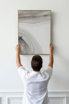 Cornice di pittura astratta psd appesa da un giovane su un muro minimo bianco
