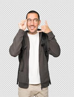 Studente stupito che fa un gesto di chiamata con la mano
