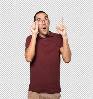Giovane stupito che indica in su con il dito
