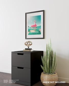 Mockup di poster con cornice artistica in cima all'armadio nero