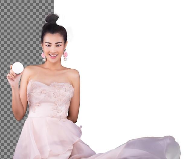 Donna asiatica indossa abito da sera rosa e gonna svolazzante di lancio o vento in aria, isolata. la ragazza degli anni '20 sorride e presenta un prodotto rotondo in polvere cosmetica vuoto, mezzo corpo su sfondo bianco da studio
