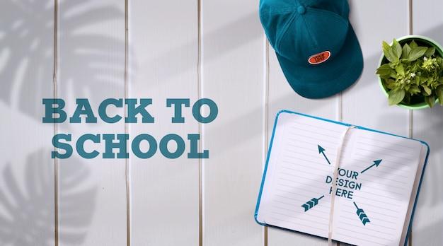 Back to school mockup notebook & cap su sfondo chiaro con ombre realistiche