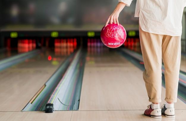 Vista posteriore della donna che gioca a bowling
