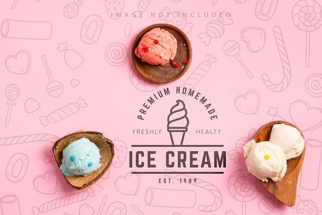 Palline di gelato o gelato colorato naturale freddo fatto in casa nei gusci organici di legno su un backround rosa pastello di mockup con lo spazio della copia. vista dall'alto.