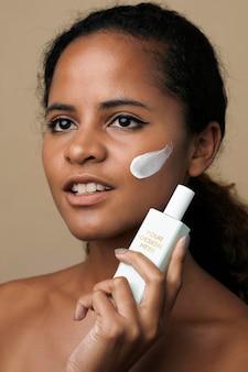 Bella donna afroamericana che tiene un mockup di contenitore di crema per il viso