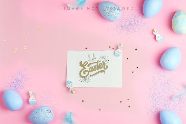 Belle uova blu pastello di pasqua con il modello del foglio di carta sulla superficie delle stelle rosa