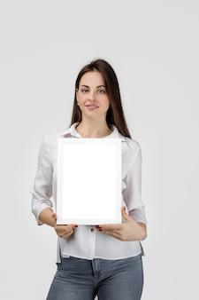 Bella donna sorridente che tiene bordo in bianco