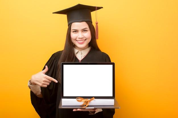 La bella donna in abito di laurea sta tenendo il modello del computer portatile