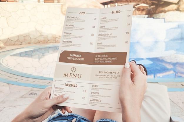 Mockup in mano del menu della spiaggia a doppia piega