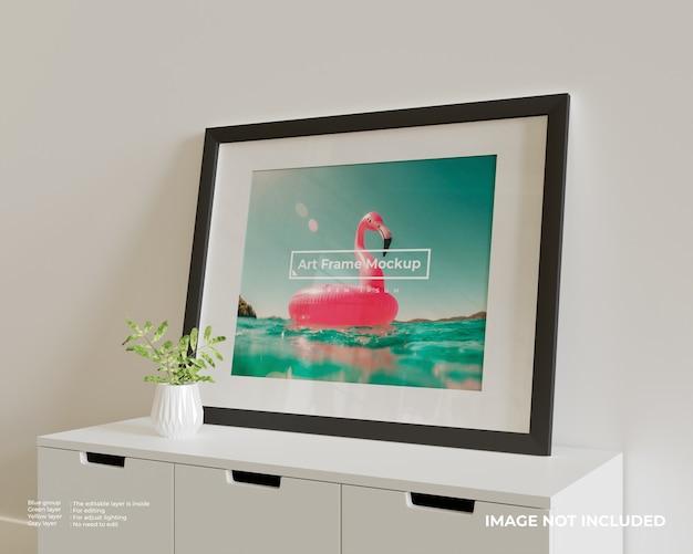 Grande mockup di poster con cornice artistica orizzontale in cima all'armadio bianco