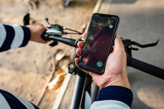 Motociclista che tiene smartphone con chiamata in arrivo