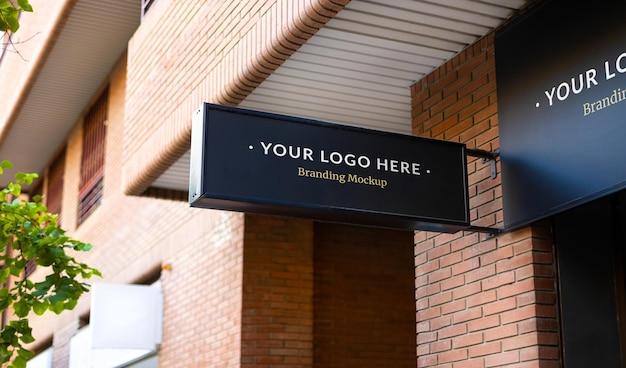 Modello di cartello commerciale nero per il design del marchio su un muro di un negozio in strada