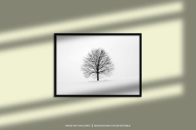 Mockup di cornice per foto orizzontale nera con sovrapposizione di ombre e sfondo di colore pastello