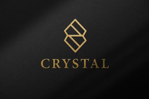 Prototipo di mockup in carta nera con stampa del logo in oro e sovrapposizione di ombre.