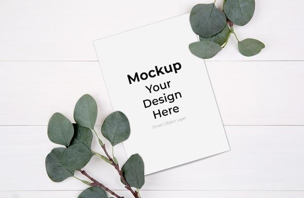 Mockup di carta in bianco e foglia sul tavolo di legno