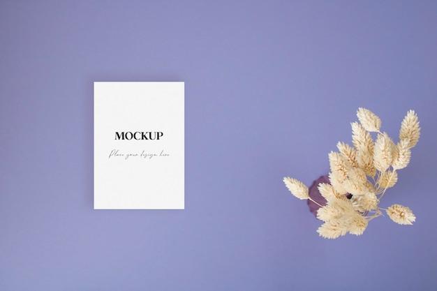 Biglietto di auguri vuoto mock up con erba secca sullo sfondo blu