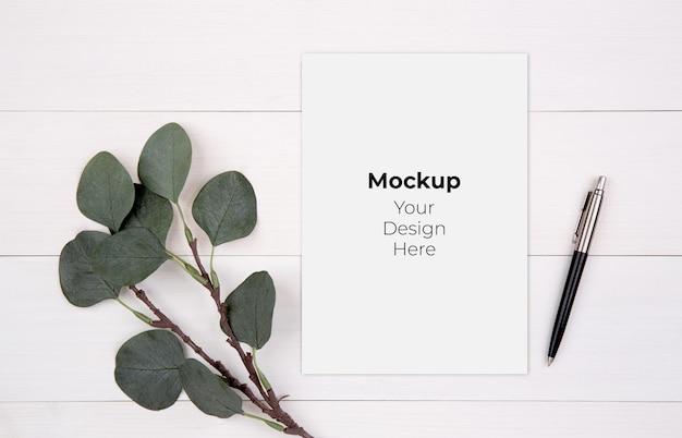Spazio della copia del foglio di carta bianco con mockup e foglia sul tavolo di legno