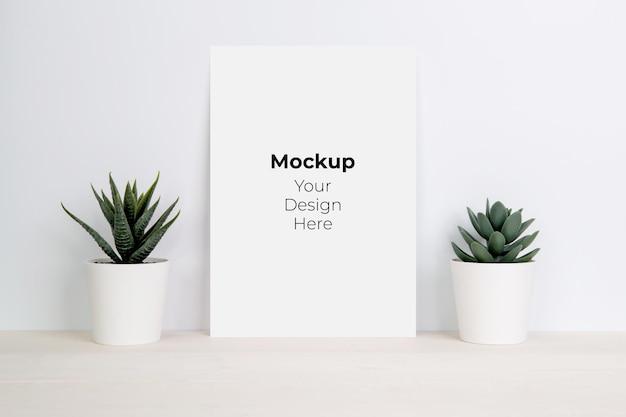 Foglio di carta bianco con mockup e piante in vaso sul tavolo di legno