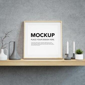 Mockup di cornice per foto in bianco sulla mensola a muro
