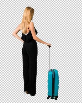 Ragazza bionda che viaggia con la sua valigia guardando indietro