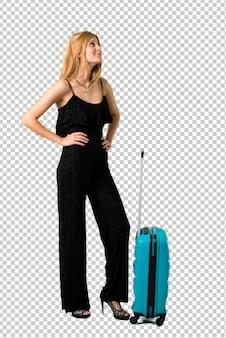 Ragazza bionda che viaggia con la sua valigia in piedi e guardando al lato