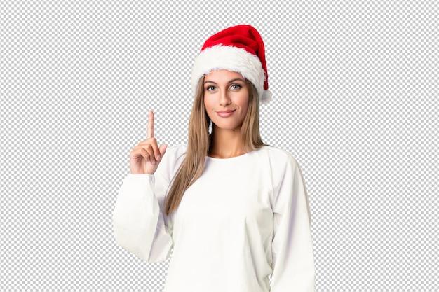 Ragazza bionda con il cappello di natale che indica con il dito indice una grande idea