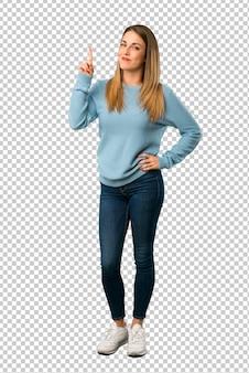 Donna bionda con la camicia blu che mostra e che alza un dito nel segno del meglio
