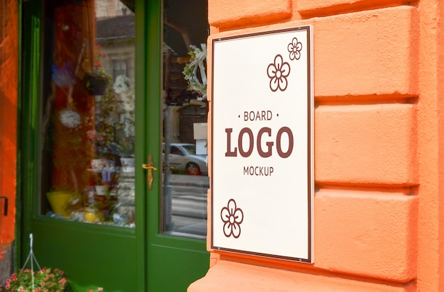 Mockup di logo di bordo sulla parete del negozio all'aperto.
