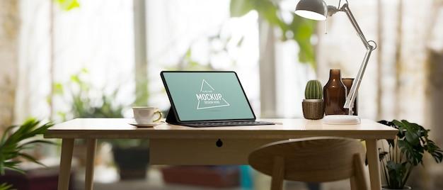 Stanza di lavoro botanica con tablet in piedi su un tavolo di legno circondato da un mockup di tablet con piante da appartamento