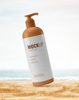 Bottiglia di pompa sul mockup della spiaggia