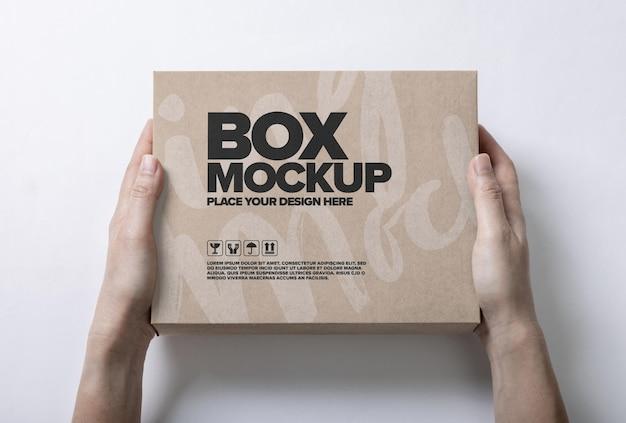 Modello di mockup di imballaggio della scatola in mano