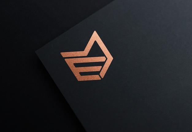 Mockup di logo in lamina di bronzo in carta nera