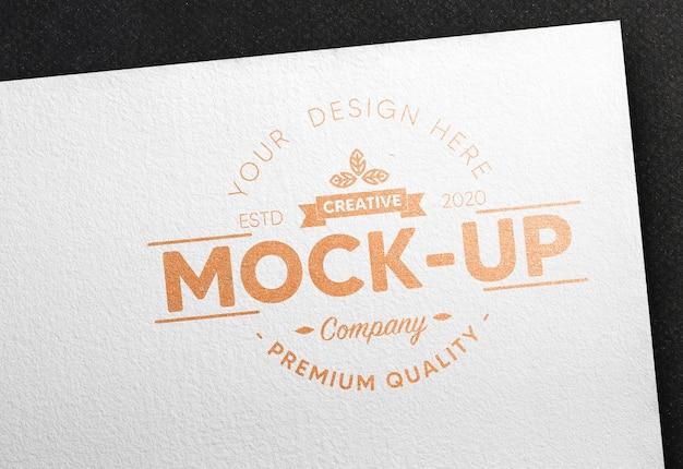 Mockup di logo in lamina di bronzo in carta bianca